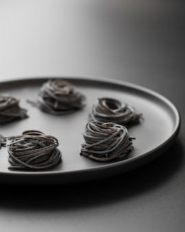 Des morceaux de pâtes sombres sur une assiette sombre