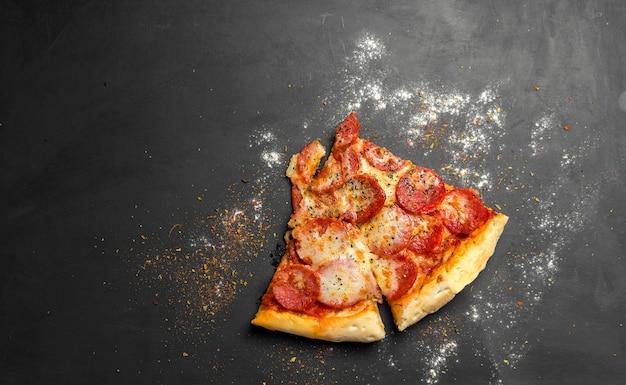 Morceaux de pizza au pepperoni sur planche de bois noir foncé, pizza italienne traditionnelle