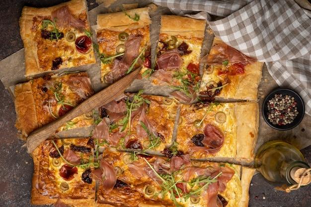 Morceaux de pizza feuilletée avec viande tranchée, roquette, olives, épices, poivre