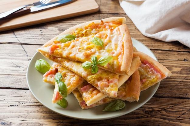 Morceaux de pizza maison sur une assiette sur une table en bois.