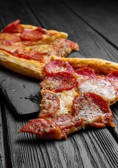 Morceaux de pizza pepperoni sur planche de bois noir foncé, pizza italienne traditionnelle