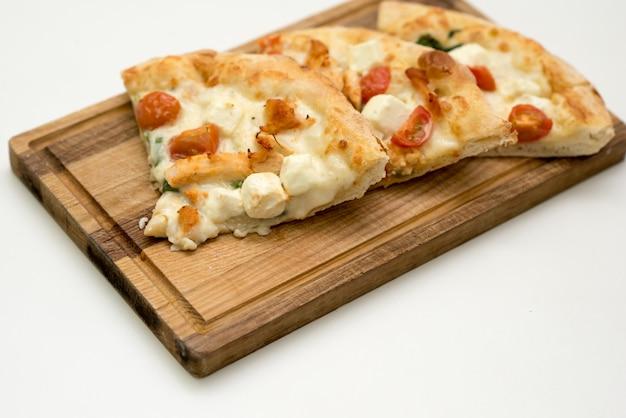 Morceaux de pizza sur une planche de bois