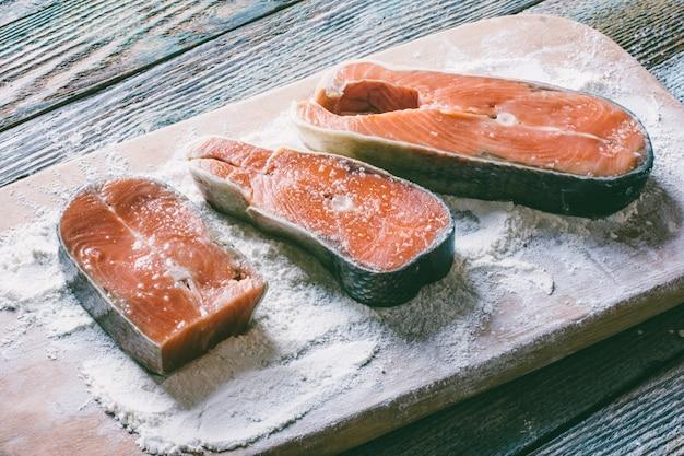 Morceaux de poisson rouge en farine sur une planche à découper