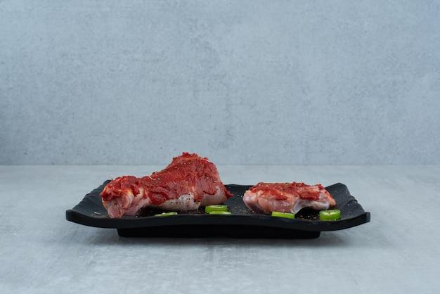 Morceaux de poulet assaisonnés sur plaque noire avec des tranches de poivre.