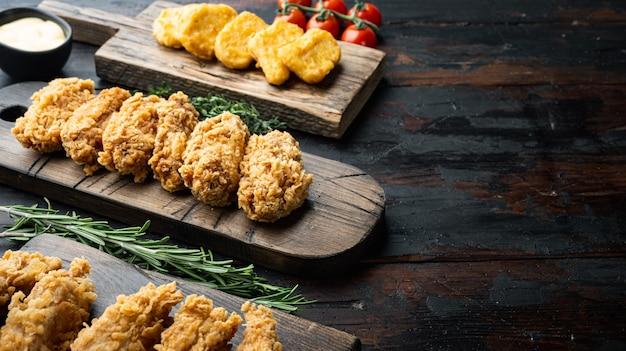 Morceaux de poulet frit pané sur table en bois sombre.