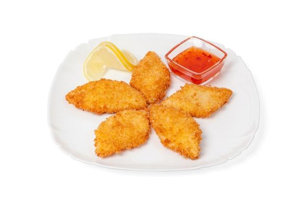 Morceaux de poulet frit servi avec sauce chili isolé sur fond blanc