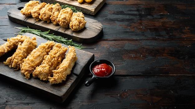 Morceaux de poulet frits croustillants faits maison sur une vieille table en bois sombre, avec espace de copie.