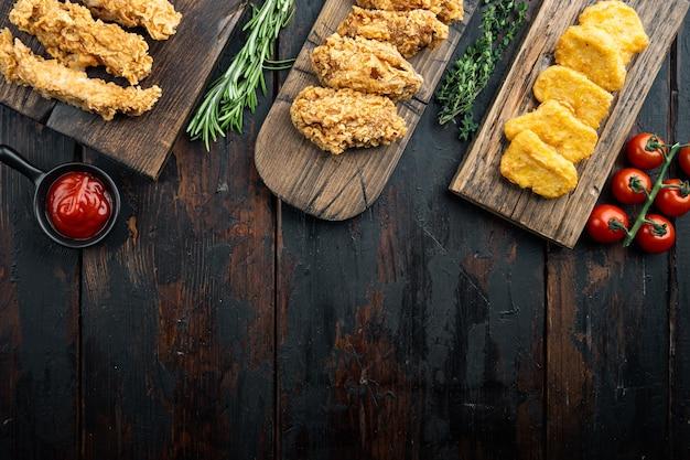 Morceaux de poulet frits croustillants faits maison sur une vieille table en bois sombre, vue de dessus, avec espace de copie.