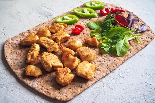 Morceaux de poulet grillés avec des légumes sur du pain mince.