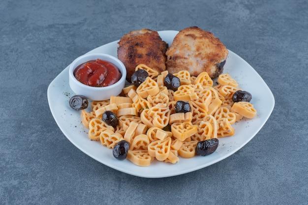 Morceaux de poulet grillés et macaronis sur plaque blanche.