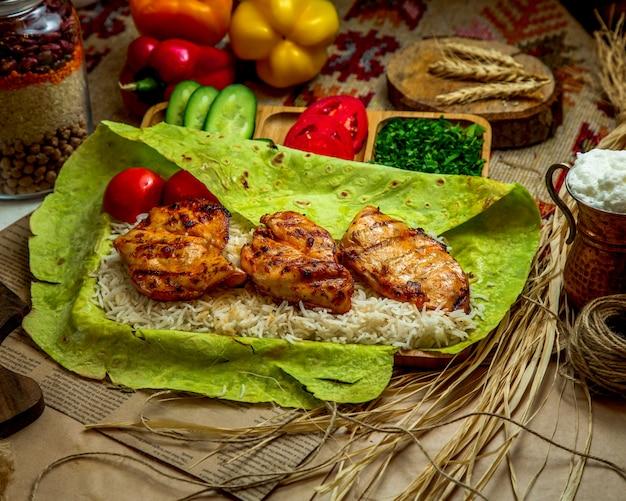 Morceaux de poulet grillés placés sur du riz à l'intérieur du pain plat vert