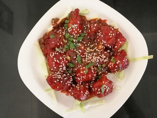 Morceaux de poulet juteux frits marinés au miel, sauce soja, épices, saupoudrés de graines de sésame sur une assiette blanche. recette asiatique, cuisine chinoise. vue de dessus, pose à plat