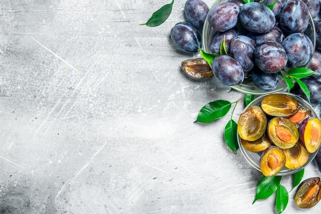 Morceaux et prunes fraîches entières dans des bols en verre. sur table rustique