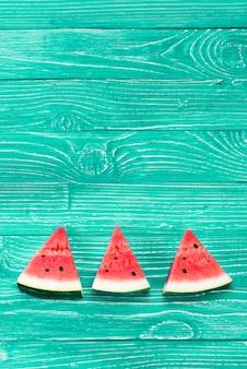 Morceaux rouges de melon d'eau fraîche sur fond vert
