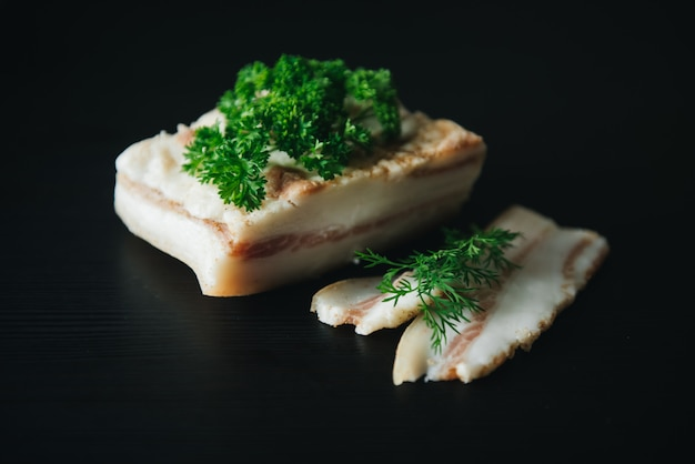 Morceaux de saindoux salé sur mur sombre. une alimentation saine avec des épices et des herbes de pranami. graisse, saindoux, suif, graisse