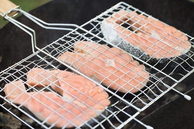Morceaux de saumon de poisson grillé sur grill chaud cuisson du poisson sur concept de charbon de bois
