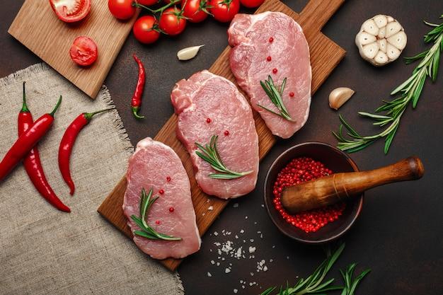 Morceaux de steak de porc cru sur une planche à découper avec mortier aux tomates cerises, romarin, ail, poivre, sel et épices