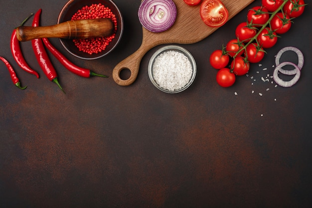 Morceaux de steak de porc cru sur une planche à découper avec tomates cerises, romarin, ail, poivron rouge, laurier, oignon
