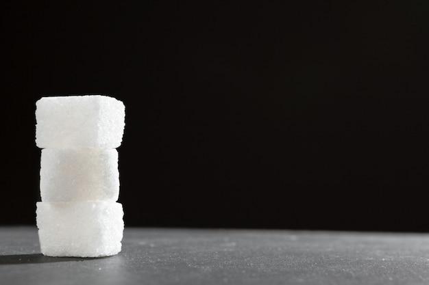 Morceaux de sucre empilés ensemble contre un noir
