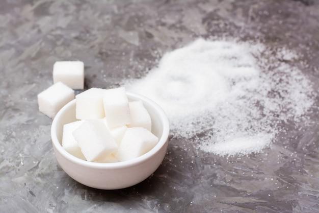Morceaux de sucre raffiné dans un bol et un tas de sable sucré sur la table