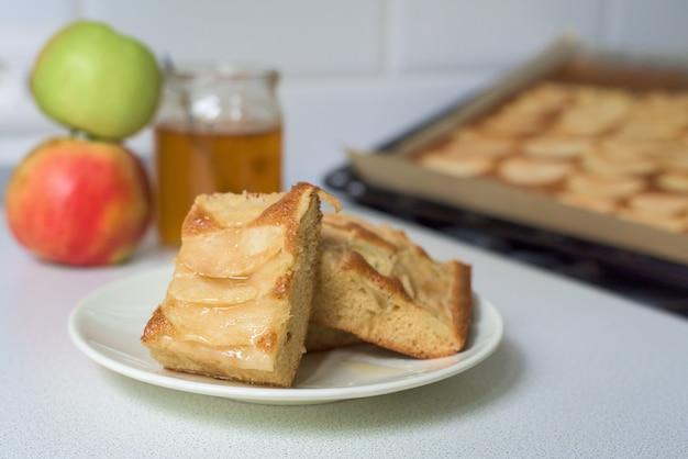 Morceaux de tarte aux pommes sur une assiette blanche avec du miel.