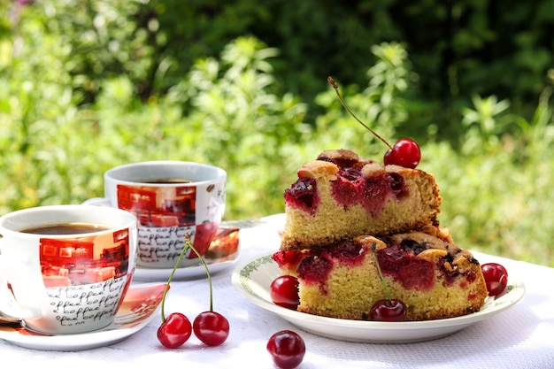 Morceaux d'une tarte avec une cerise et deux tasses de café sur une table à l'extérieur, photo horizontale