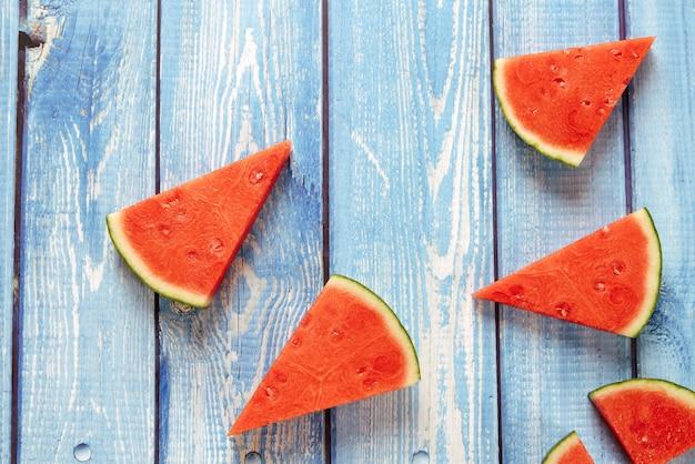 Morceaux triangulaires de pastèque sur une table en bois bleue
