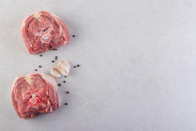 Morceaux de viande d'agneau crue placés sur une table en pierre.