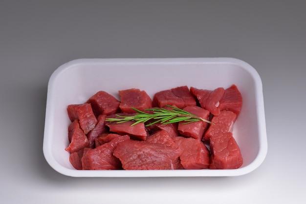 Morceaux de viande de boeuf crue fraîche dans un plateau en plastique sur fond gris tranches de boeuf haché