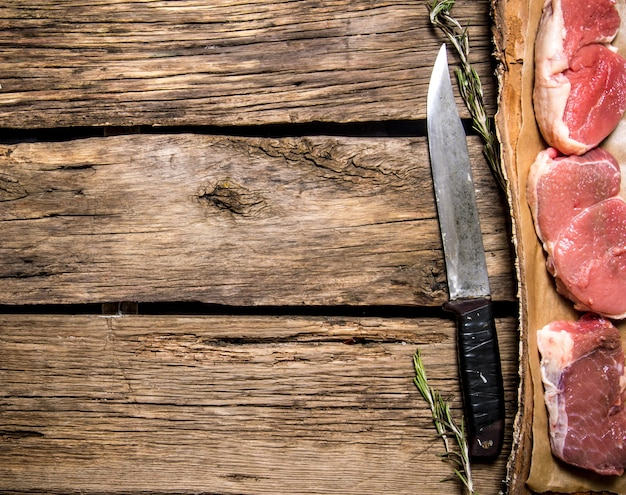Morceaux de viande crue avec un couteau de boucher. sur fond en bois. espace libre pour le texte. vue de dessus