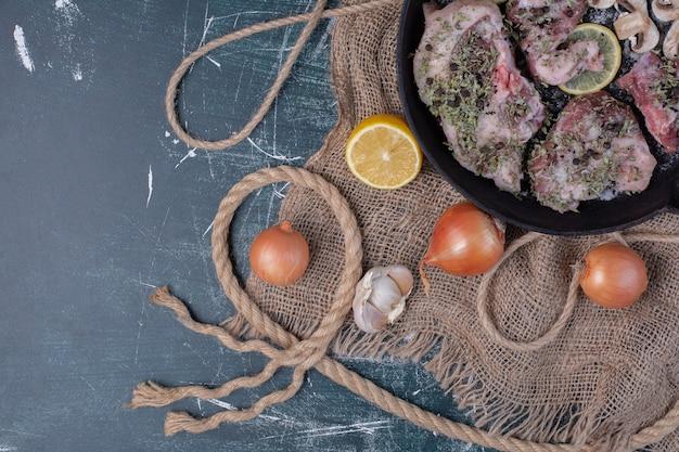 Morceaux de viande crue dans une poêle noire avec oignons, ail, citron et champignons.