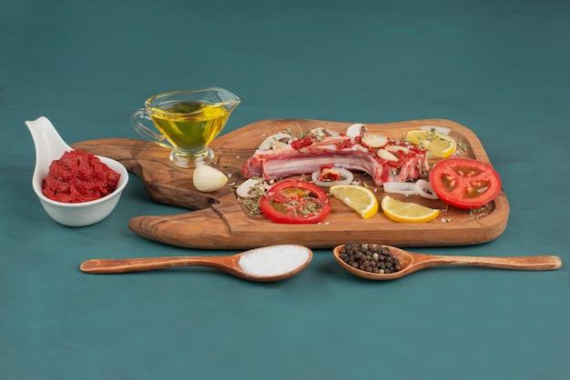 Morceaux de viande non cuits avec légumes, huile et épices sur table bleue.