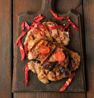 Des morceaux de viande de porc grillés sur le gril se trouvent sur une planche de bois vintage