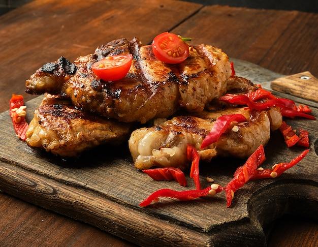 Des morceaux de viande de porc grillés sur un grill se trouvent sur une planche de bois vintage