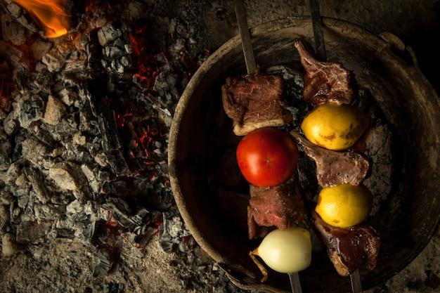 Morceaux de viande à la tomate et au citron cuits sur des charbons ardents le plat est cuit et fumé sur du charbon de bois