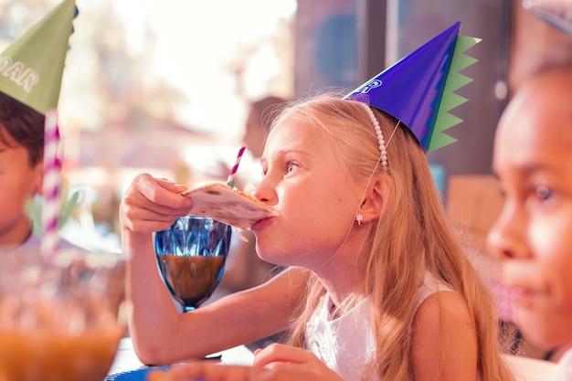Mordant. fille blonde calme portant un chapeau de fête et mordant la pizza tout en ayant faim