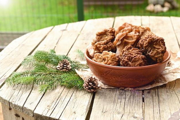 Morilles dans un bol en céramique brune sur une table en bois en plein air
