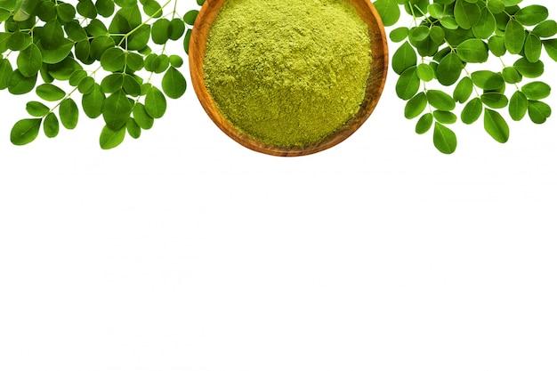 Moringa en poudre (moringa oleifera) dans un bol en bois avec des feuilles de moringa fraîches originales isolées sur fond blanc.