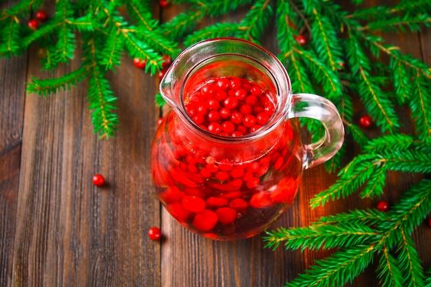 Morse ou thé de myrtille dans un pichet en verre entouré de branches de sapin sur une table en bois.
