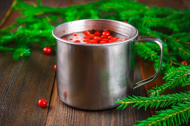 Morse ou thé de myrtille dans une tasse en étain, entourée de branches de sapin sur une table en bois.