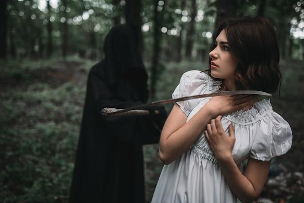 La mort balançant une faux sur une jeune femme victime