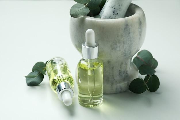 Mortier à l'eucalyptus et flacons compte-gouttes d'huile sur fond blanc
