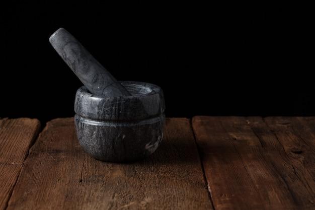 Mortier en marbre sur une vieille table en bois sur fond noir.