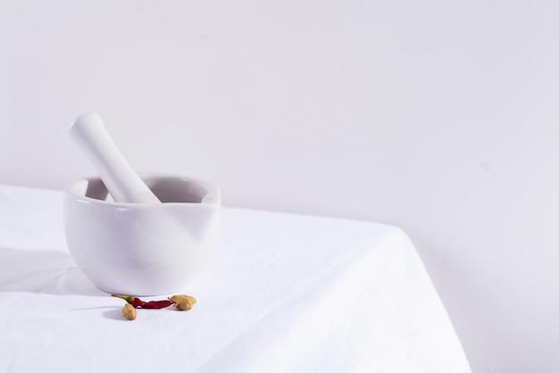 Mortier et pilon en porcelaine blanche avec piments et cardamome isolé sur table textile, espace copie