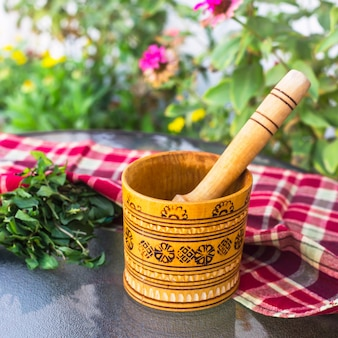 Mortier de village en bois pour herbes et épices avec menthe à l'intérieur