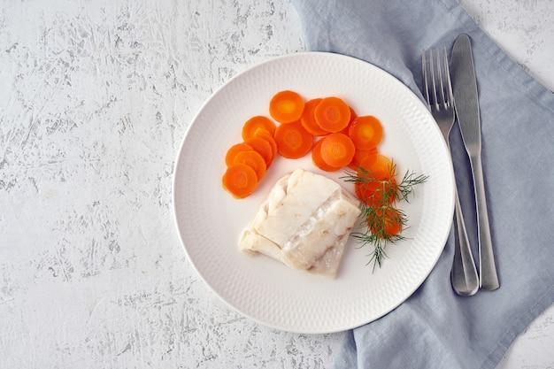 Morue bouillie avec carotte et aneth sur plaque blanche