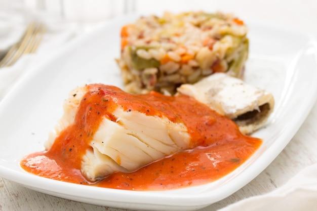 Morue bouillie avec sauce tomate et riz sur plaque