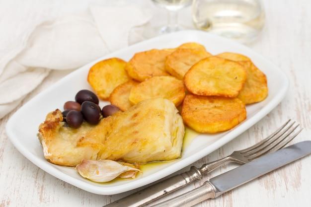Morue frite avec pomme de terre sur plat blanc