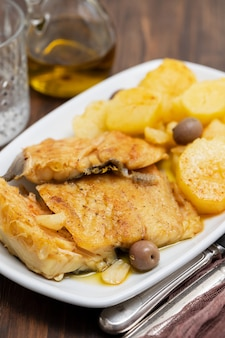 Morue avec pomme de terre frite sur plat blanc