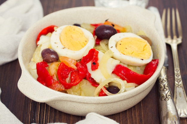 Morue avec pomme de terre, poivron rouge, œuf et olives sur plaque